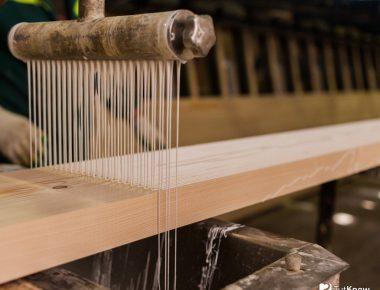 нанесение клея на доски на производстве бруса